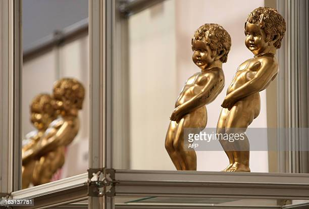 Models of the Mannekin Pis statue stand on a shelf at the stand for Brussels at the ITB Berlin tourism convention prior to its opening in Berlin on...