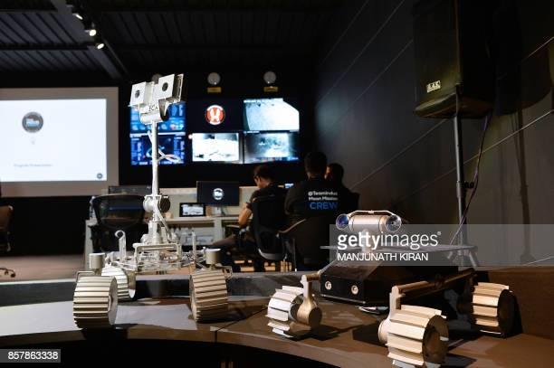 Models of the unmanned lunar rovers developed by 'Team Indus' sit at the organisation's lunar mission command and control centre during a...