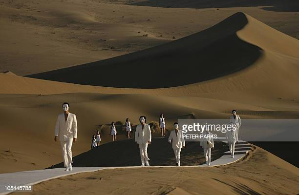 Models parade on a catwalk in the desert of Whistling Sand Mountain on the outskirts of Dunhuang in China's northwest Gansu province for iconic...