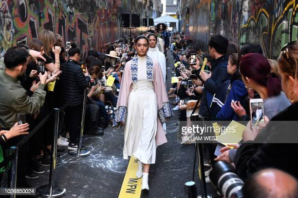 Models parade outfits by Australian label Asiyam during a Melbourne Fashion Week show in an innercity laneway on September 5 2018