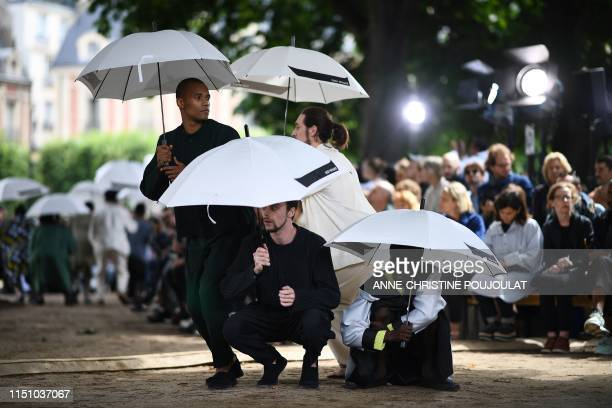 Models perform as they present a creation for Homme Plisse by Japanese fashion house Issey Miyake during the Men's Spring/summer 2020 fashion...
