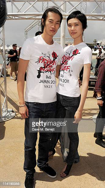 Models Philip Huang and Tao Okamoto pose during a photocall for model Naomi Campbell's charity Fashion For Relief Japan Appeal at the Majestic Beach...