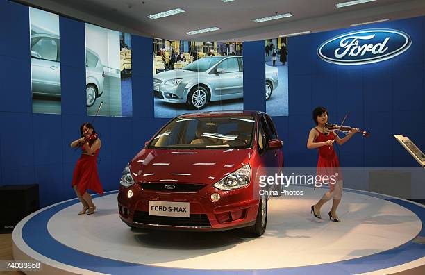 Models play violins beside a Ford SMAX during a family car fair on May 1 2007 in Nanjing of Jiangsu Province China Cars with an engine size of less...