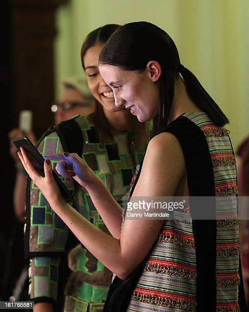 Models play with there iPads backstage at the Nova Chiu show during London Fashion Week Fall/Winter 2013/14 at Freemasons Hall on February 15, 2013...