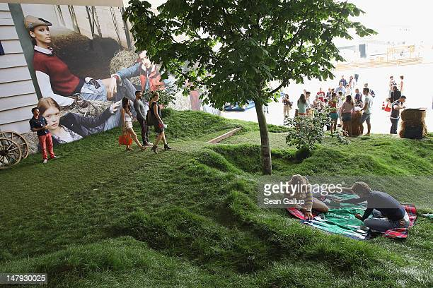 Models playing backgammon recline on real grass as visitors walk past at the Hilfiger Denim stand at the 2012 Bread Butter fashion trade fair at...