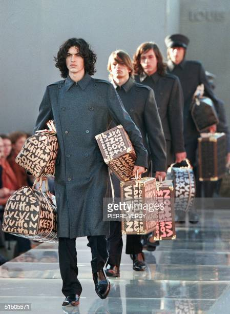 Models playing porter, present creations and luggage for Louis Vuitton 11 October 2000 in Paris during the Spring/Summer 2001 ready-to-wear...