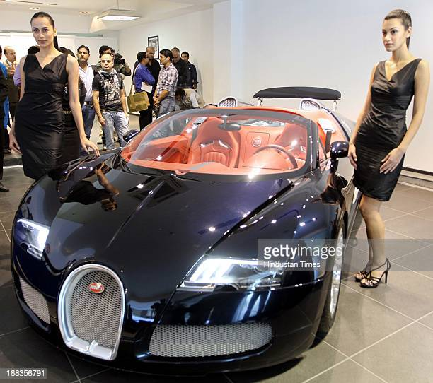 Models pose as front of Bugatti Veyron 164 Grand sports car during its India launch on October 28 2010 in New Delhi India The Bugatti Veyron debuts...