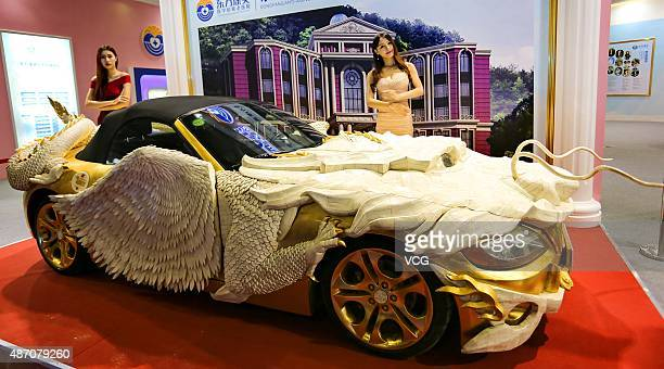 Models pose at a BMW Z4 decorated with Yak bone carving and pure gold during an exhibition on September 5 2015 in Guangzhou China Carving artist Su...