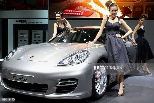 Models pose beside the world premiere display of the Porsche Panamera car during a special media opening of the Auto Shanghai 2009 at Shanghai New...