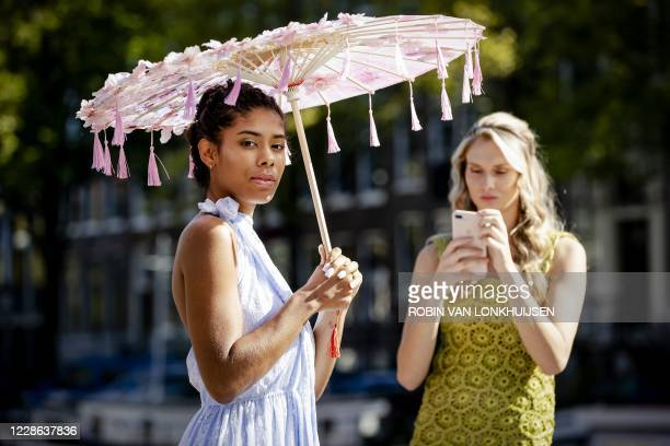 Models pose during the modified ninth edition of the Canal Catwalk, the annual fashion show along the canals of Amsterdam on September 21, 2020. /...
