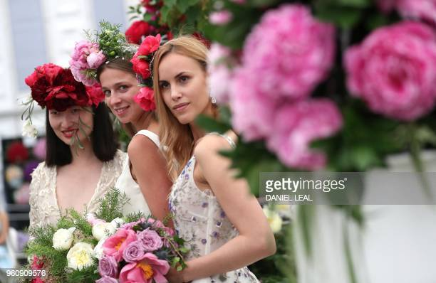 Models pose for a photgraph as they stand at the Primrose Hall peony display during a visit the 2018 Chelsea Flower Show in London on May 21 2018 The...