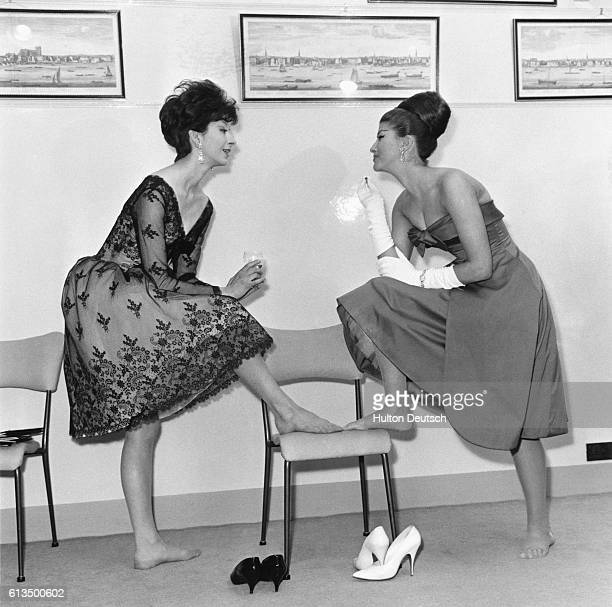 Models pose in evening wear at a Susan Small fashion show in London L Christine wears a Chantilly lace dinner dress while R Jacki sports a satin...