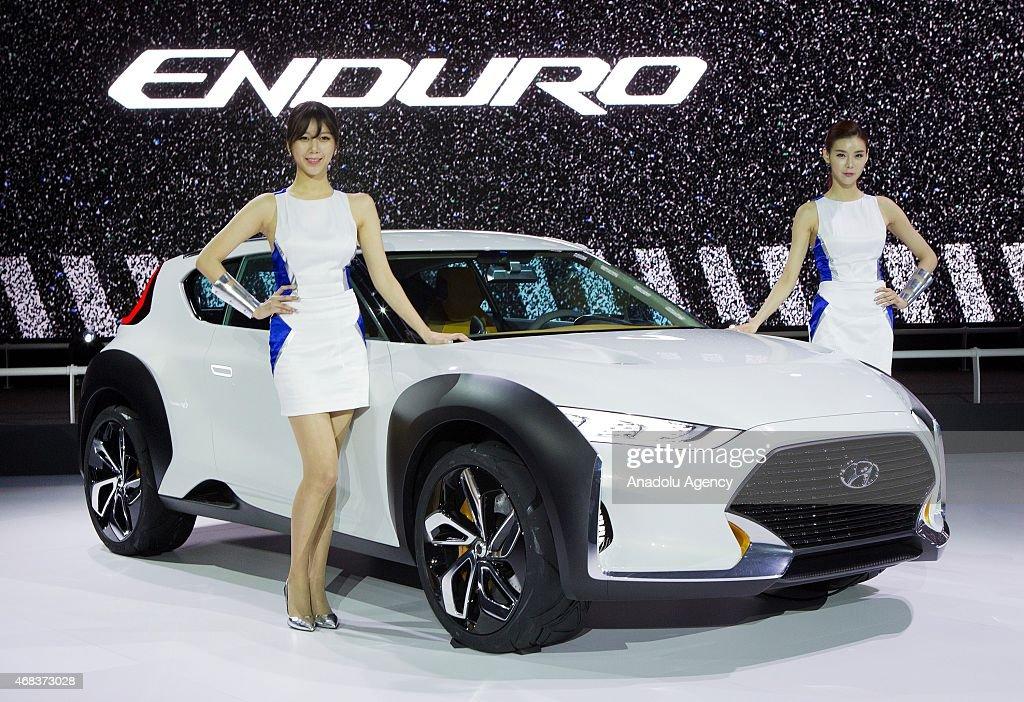 Models Pose Next To A Hyundai Enduro At The Seoul Motor Show 2015 At