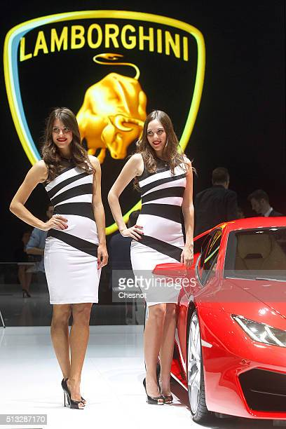 Models pose next to a Lamborghini Huracan automobile during the second press day of the 86th Geneva International Motor Show on March 2 2016 in...