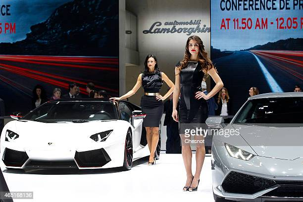 Models pose next to a lamborghini Huracan during the press day at the 85th Geneva International Motor Show on March 3 2015 in Geneva Switzerland The...