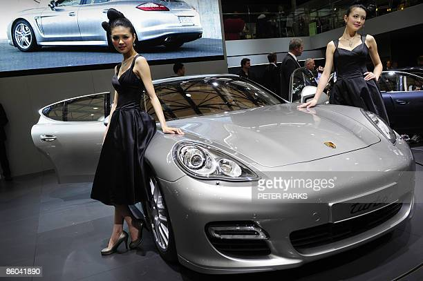 Models pose next to a Porsche Panamera, a new four-door sports car making its international debut at Auto Shanghai 2009, China's largest auto show on...