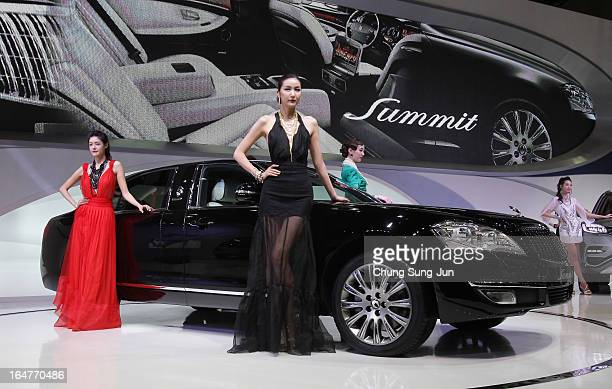 Models pose next to a Ssangyong Chairman W Summit at the Seoul Motor Show 2013 on