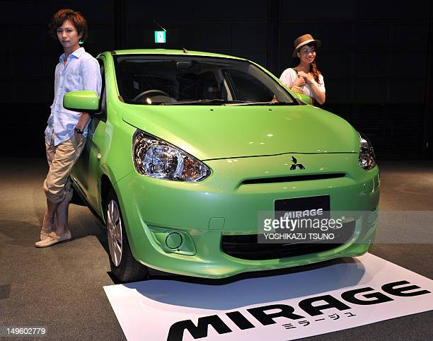 Models pose next to Japan's car manufacturer Mitsubishi Motors new global compact car Mirage in Tokyo on August 1 2012 The Mirage which is equipped...