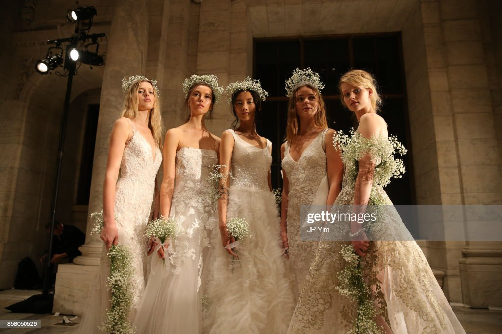 Models pose on the runway at the Reem Acra FW 2018 Bridal Show at the New York Public Library on October 5, 2017 in New York City.