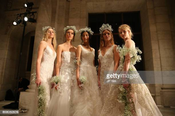 Models pose on the runway at the Reem Acra FW 2018 Bridal Show at the New York Public Library on October 5 2017 in New York City