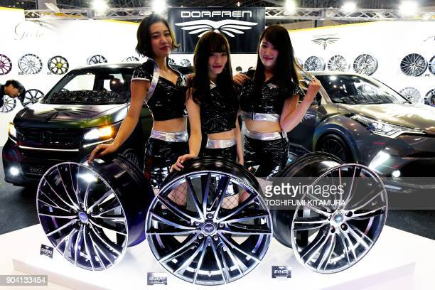 Models pose with Dorfren wheels at the company's booth of the Tokyo Auto Salon at the Makuhari Messe in Chiba on January 12 2018 The exhibition one...