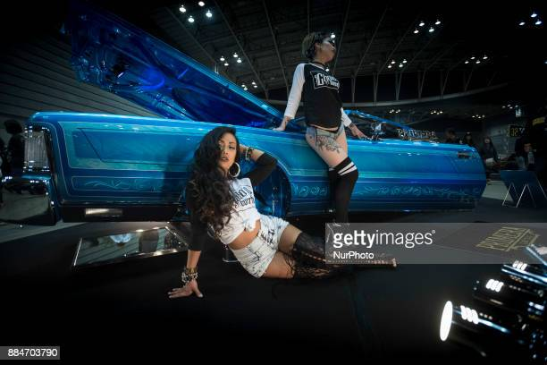 Models poses for the cameras next to the custom hot rod car is shown during the 26th Annual Yokohama Hot Ror Custom Show 2017 December 3 2017 in...