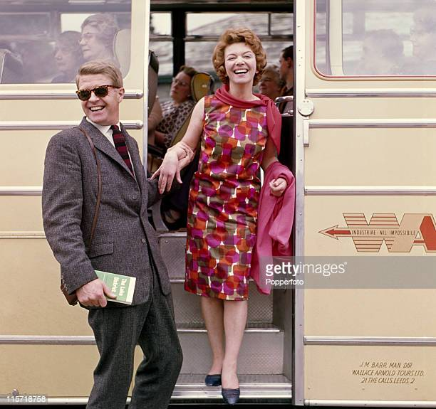Models posing as a young middleaged couple on holiday alighting from a coach he is wearing a tweed jacket twill trousers and a necktie and she in a...