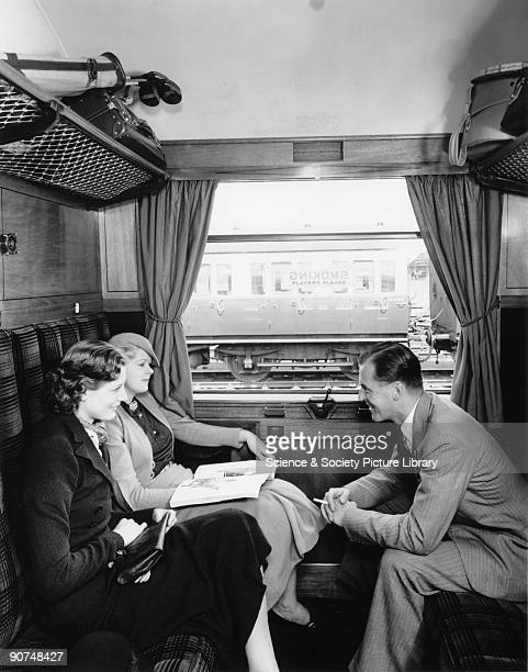 Models posing in the compartment of a railway carriage preliminary photograph taken for a poster to advertise GWR's 'Cornish Riviera' service from...