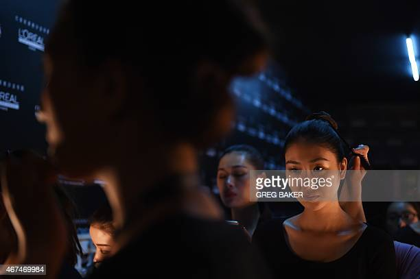 Models prepare backstage before parading during the 23rd China International Young Fashion Designers Contest at China Fashion Week in Beijing on...