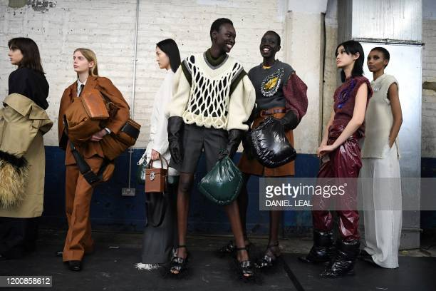 Models prepare to present creations by fashion house TOGA ahead of their catwalk show for the Autumn/Winter 2020 collection on the second day of...