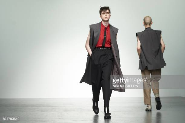 Models present creations by British fashion house John Lawrence Sullivan during a catwalk show at London Fashion Week Men's June 2017 in London on...