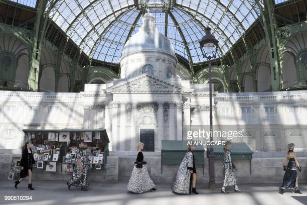TOPSHOT Models present creations by Chanel at the end of the 20182019 Fall/Winter Haute Couture collection fashion show in front of a replica of the...