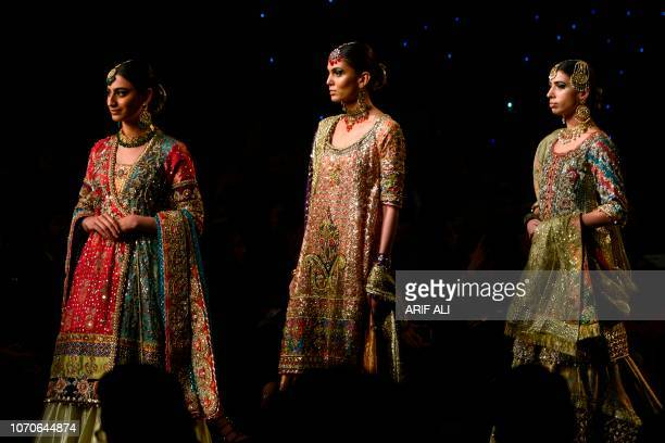 Models present creations by designer Dnnus Dlrar during a fashion show of the Pantene Hum Bridal Couture Week in Lahore on December 9 2018