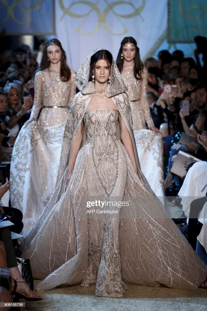 Models present creations by Elie Saab during the 2017-2018 fall/winter Haute Couture collection in Paris on July 5, 2017. / AFP PHOTO / Patrick KOVARIK
