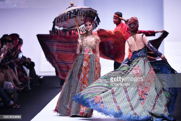 Models present creations by Indonesian designer Anne Avantie during the 2019 Jakarta Fashion Week to seek donations for fishermen in Palu and...
