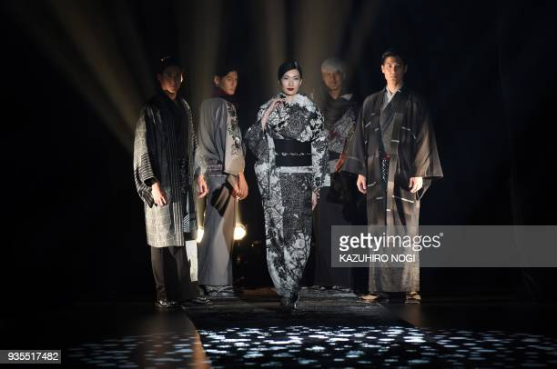 Models present creations by Japanese designer Jotaro Saito for his 2018 autumn/winter collection at Tokyo Fashion Week in Tokyo on March 21 2018 /...