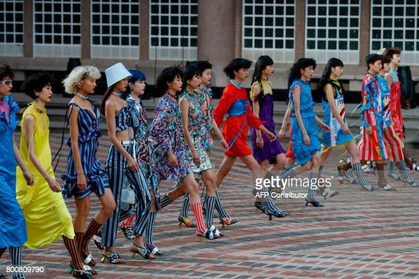 Models present creations by Kenzo during the Men's Fashion Week for the Spring and Summer 2018 collection in Paris on June 25 2017 / AFP PHOTO /...