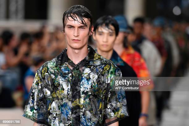 Models present creations by Louis Vuitton during the Men's Fashion Week for the Spring/Summer 2018 collection in Paris on June 22 2017 GUAY