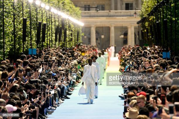 Models present creations by Louis Vuitton fashion house during the men's spring/summer 2019 collection fashion show on June 21 2018 in Paris