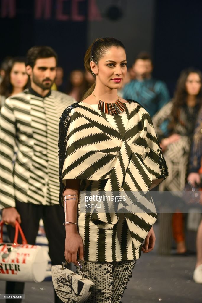 Models present creations by Pakistani fashion designer