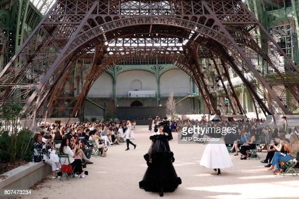 TOPSHOT Models present creations for Chanel under a replica of the Eiffel Tower at the Grand Palais during the 20172018 fall/winter Haute Couture...