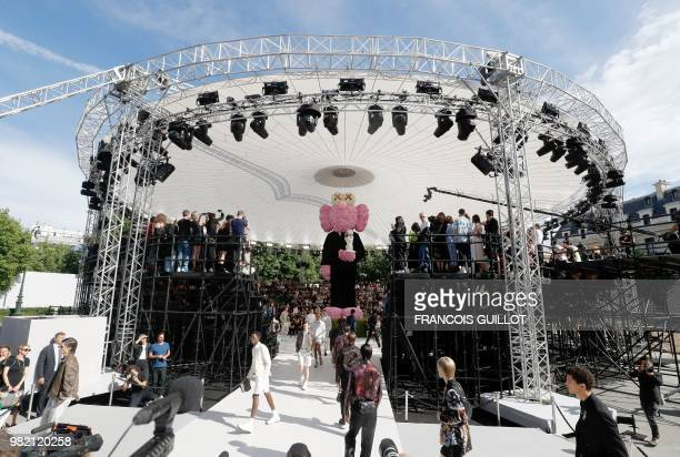 Models present creations for Dior during the Men's Spring/Summer 2019 fashion show on June 23 2018 in Paris