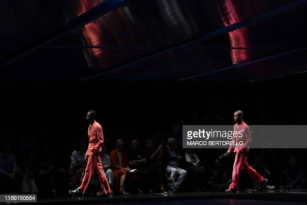 Models present creations for fashion house Emporio Armani during the presentation of its men's spring/summer 2020 fashion collection in Milan on June...
