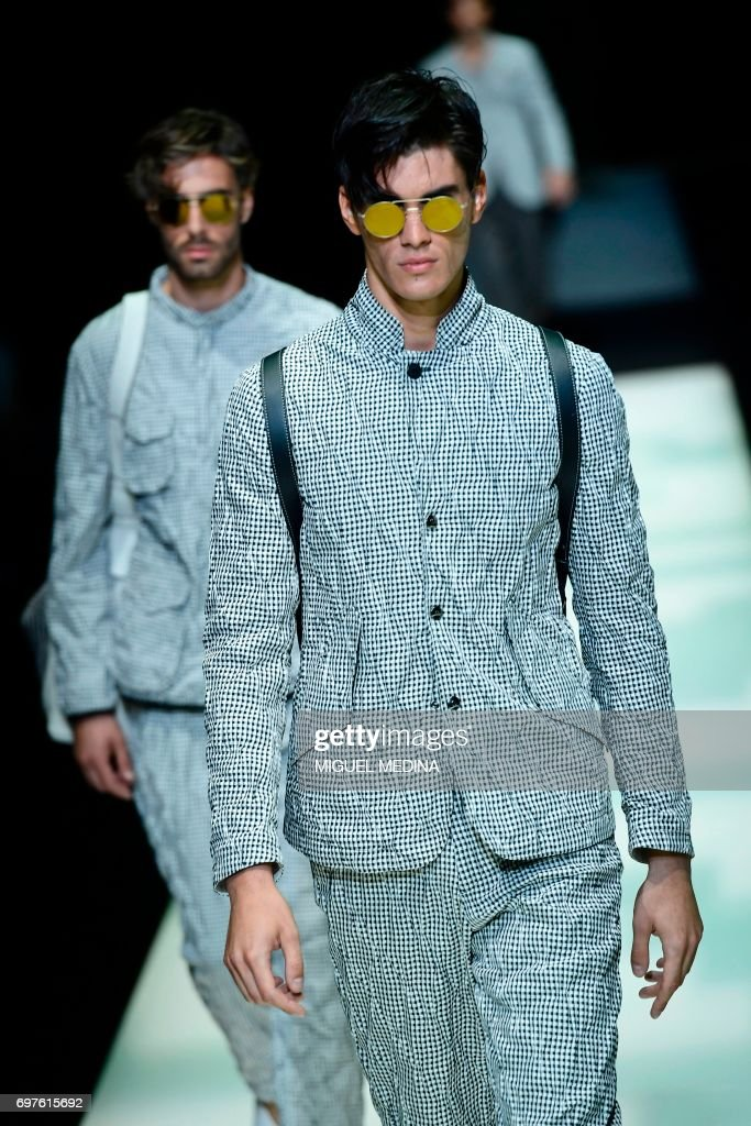Models present creations for fashion house Giorgio Armani during the Men's Spring/Summer 2018 fashion shows in Milan, on June 19, 2017. / AFP PHOTO / Miguel MEDINA