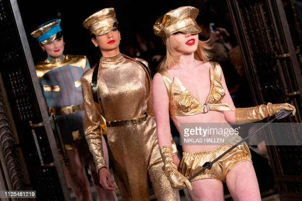 Models present creations from British designer Pam Hogg during her 2019 Autumn / Winter collection catwalk show at London Fashion Week in London on...