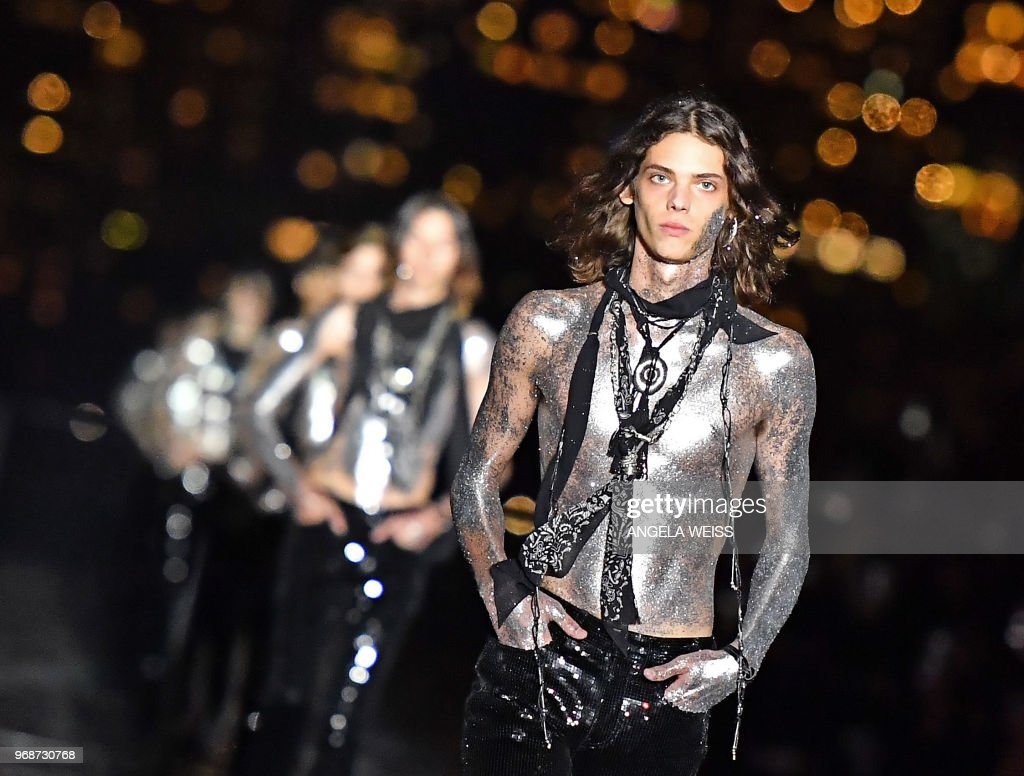 TOPSHOT - Models present creations from the Saint Laurent Men's Spring/Summer 2019 collection during a runway show in Liberty State Park on June 6, 2018 in Jersey City, New Jersey.