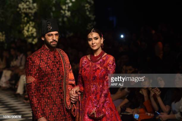 Models present creations of designer Nomi Ansari during the Pakistan Fashion Design Council L'Oreal Paris Bridal Week 2018 in Lahore on September 4...