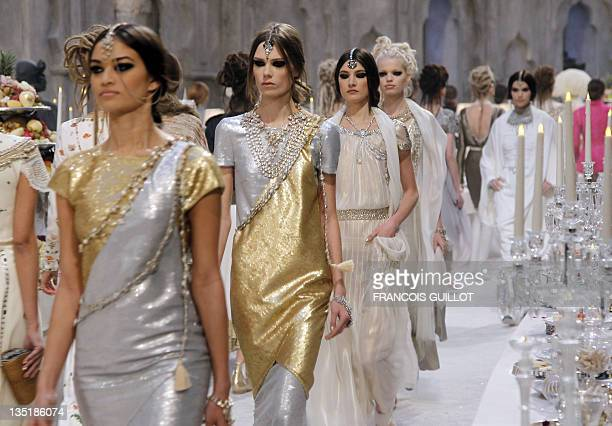 Models present outfits by Germanborn fashion designer Karl Lagerfeld during the Chanel Metiers d'Art PreFall collection show entitled ParisBombay on...