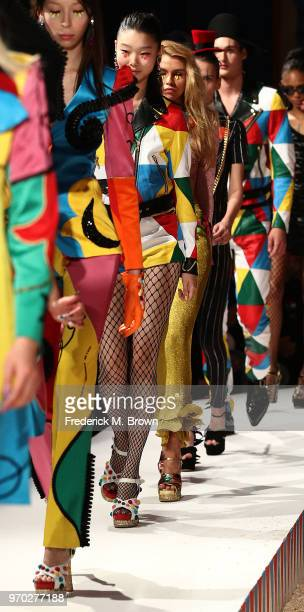 Models present outfits during Moschino Spring/Summer 19 Menswear and Women's Resort Collection at the Los Angeles Equestrian Center on June 8 2018 in...