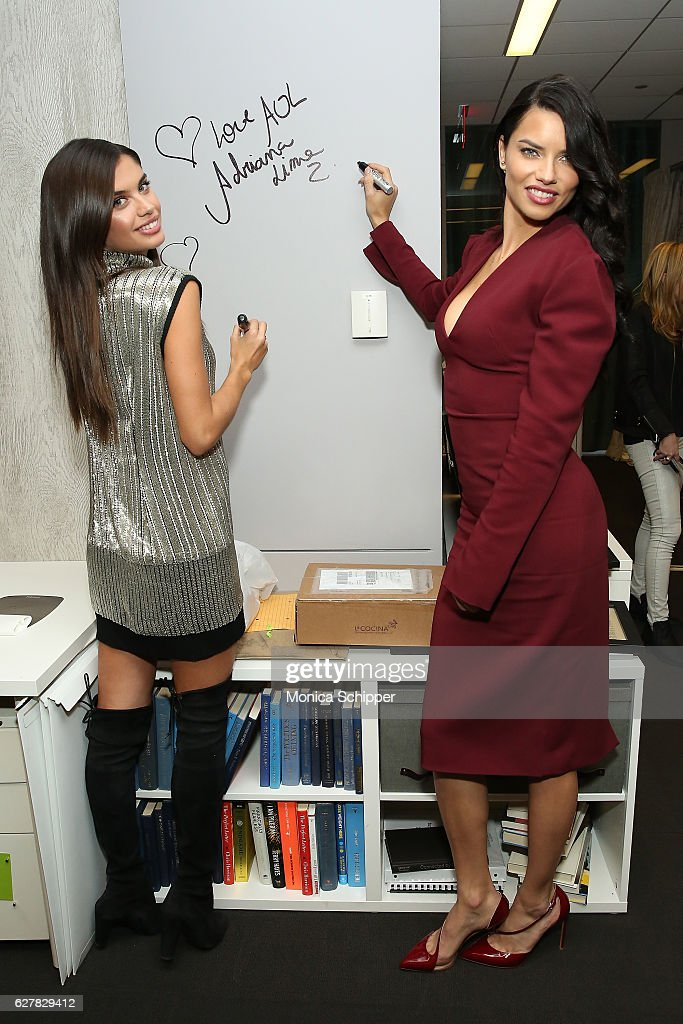 Models Sara Sampaio (L) and Adriana Lima sign the wall at AOL HQ when they visit for Build Presents Victoria's Secret Angels Sara Sampaio and Adriana Lima at AOL HQ on December 5, 2016 in New York City.